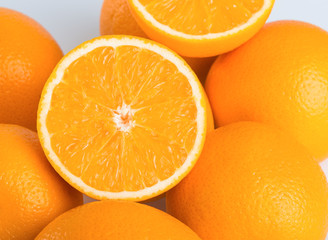 Fresh orange and cut in half on white background