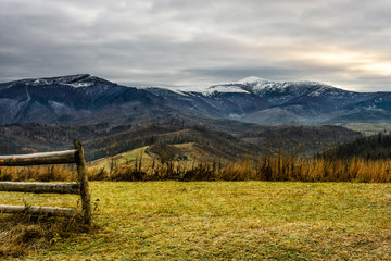 fence on the meadow in snowy mountains