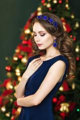 Portrait a beautiful woman near christmas tree