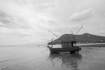 fishing boat on the beach after sea tide black and white tone at Bangsarey near Pattaya, Thailand