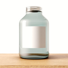 One empty jar of transparent glass with closed metal cap on the wood desk.White wall at background.Clean glassy container and gray mockup label.Drinks,food storage concept.3d rendering.