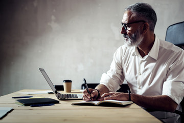 Adult stylish businessman wearing a classic glasses and working with laptop at the wood table in modern loft.Bearded middle age man making notes notebook. Horizontal,blurred background. Wall mural