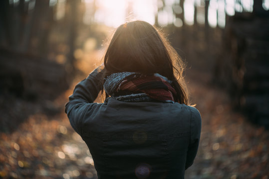 Close up back view of woman in forest watching sunset