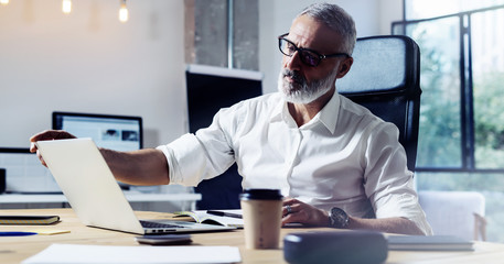 Middle age top manager wearing a classic glasses and working at the wood table in modern interior design office.Stylish bearded businessman using laptop on workplace. Horizontal wide,blurred. Wall mural