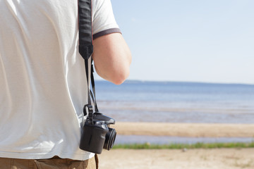 Man (male) dressed in shirt and breeches, standing on  sandy shore of  sea and holding camera
