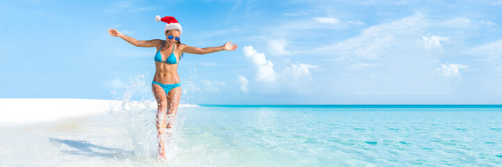 Christmas beach holiday travel banner panorama background for Christmas vacation fun. Bikini woman running carefree splashing water enjoying swim caribbean travel getaway with santa hat.