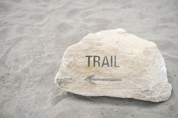 Trail message engraved in rock pointing the way on wilderness hiking sand background