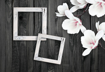 White magnolia flowers and photo frame on background of shabby w
