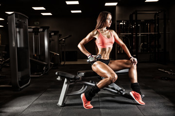 Fitness young sexy girl in the gym doing exercises with dumbbell
