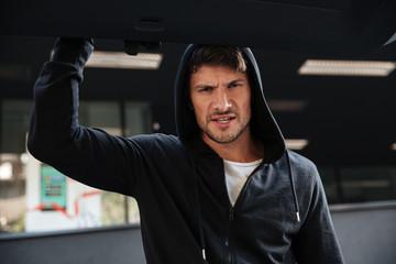Angry criminal man closing car trunk outdoors