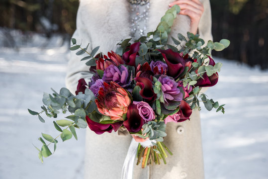 Wedding bouquet in hands of the bride. Winter time, snowy forest