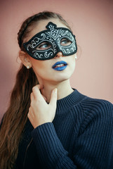 Beautiful girl with black venetian mask