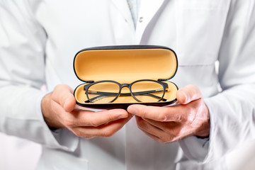 Ophthalmologist in uniform holding glasses for sight in yellow case. Close-up view focused on glasses