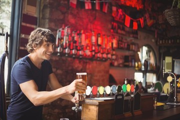 Bar tender offering glass of beer to customer