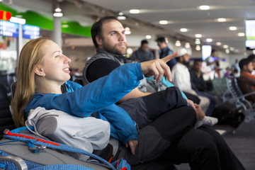 Man and woman sitting at airport terminal and pointing