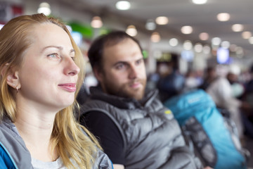 Man and woman sitting at airport terminal