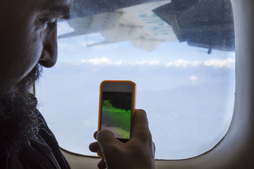 Bearded man sitting at airplane window and taking photo on telephone