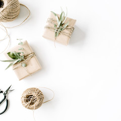 creative arrangement pattern of craft boxes and green branches on white background. flat lay, top view