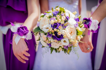 bride and bridesmaids with violet bracelets on hands