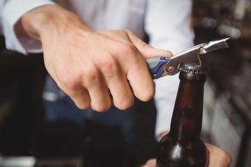 Close-up of bartender opening a beer bottle
