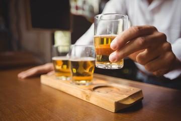 Close-up of bartender holding whisky shot glass at bar counter