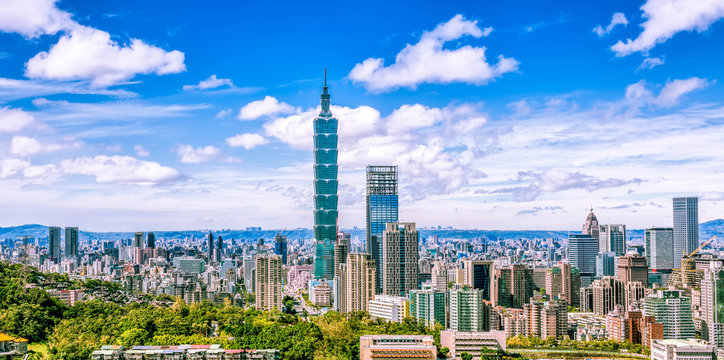Aerial panorama over Downtown Taipei, capital city of Taiwan with view of prominent Taipei 101 Tower amid skyscrapers in Xinyi Financial District & overcrowded buildings in city center under sunny sky