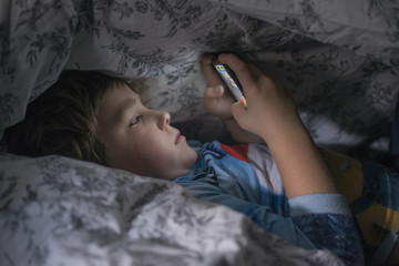 Young boy playing with cell phone under duvet
