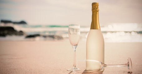 Champagne bottle and two flutes on sand