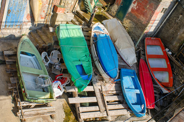Different colorful boats stored under the Genoa Nervi promenade on a sunny day in Italy