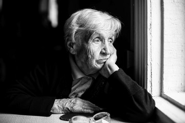 Elderly woman sadly looking out the window, a black-and-white photo.