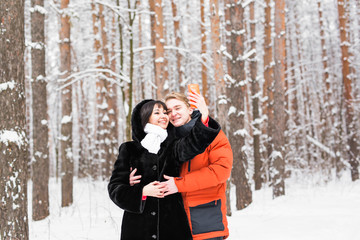 people, season, love, technology and leisure concept - happy couple taking photo with smartphone on over winter background