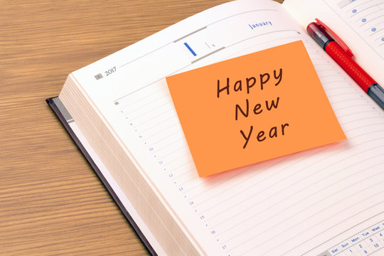 Orange sticky note on a new year 2017 office organizer. Happy New Year