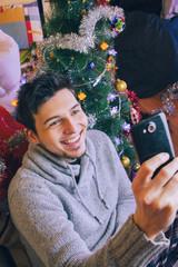 Hombre joven tomándose una foto con su teléfono móvil en su casa en navidad
