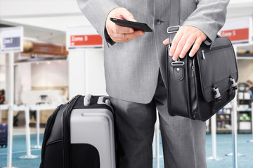 Traveling businessman with his luggage using phone at the airport
