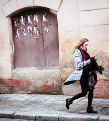 trendy women in stylish clothing with a warm scarf walking down