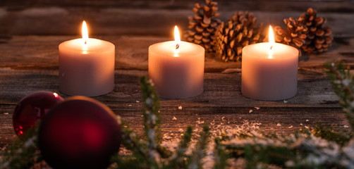 Christmas winter candlelight with candles and tree bulb on wood
