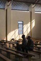 Two Rwandan men in school benches in a school for adults in Kigali, Rwanda.