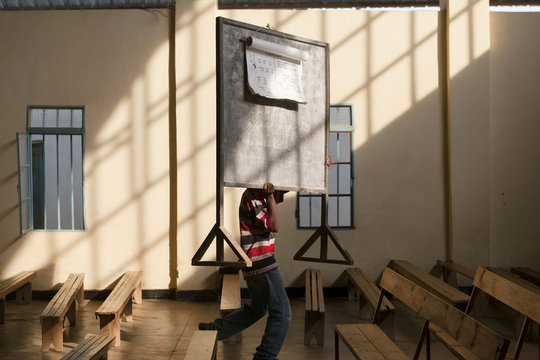 A man in a school for adults in Kigali, Rwanda carrying a chalk board.