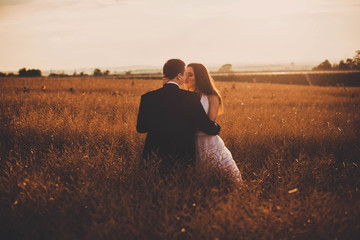beautiful and young bride and groom kiss each other in a field