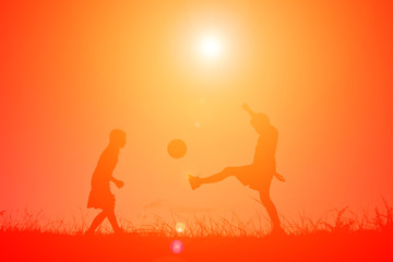 Silhouette children playing football on the sky sunset. Time on holiday