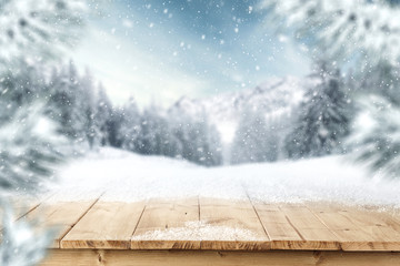 Table of wooden top and free space for your decoration of text or product. Landscape of mountains at winter time. Blurred branches of spruce and frost.