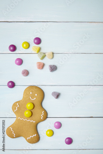 Hand Decorated Gingerbread Man On A Painted Wooden Table Background