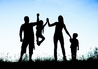 Silhouette of parents and kid having fun spending time
