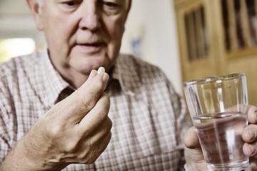 Senior nimm seine Meikamente ein, Tabletten, Medizin