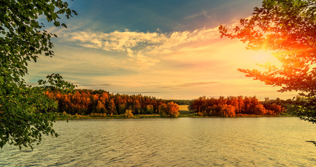evening sun over river. trees in the forest under sunshine at sunset. colorful sky.  majestic landscape. dramatic picturesque summer scene. beauty in the world. vintage style. instagram toning effect