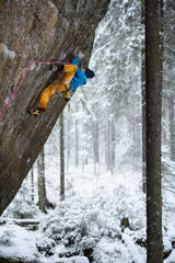 Mountain climber ascending a rock in winter snowy forest. Extrem sports. Karelian nature.