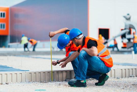 Construction workers. Construction workers measuring