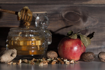 When is could outside , you can make delicious warm tea with ginger and jar of honey and nuts. Apple on the table. Honey flow from honey spoon. The leaf on the red Apple