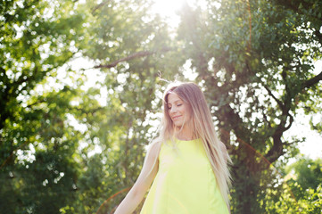 Beautiful young woman with long blonde hair. Sunny summer.