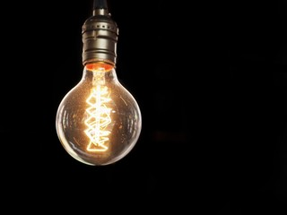 Isolated glowing modern light bulb on black background
